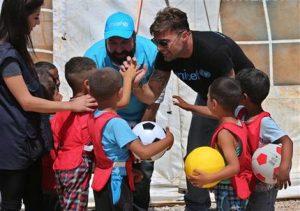 """En esta foto del jueves 2 de junio del 2016, Ricky Martin, a la derecha, visita a niños sirios en un campamento informal de refugiados sirios en Minnieh, cerca de la ciudad norteña de Tripoli, en el Líbano. El superastro puertorriqueño, embajador de buena voluntad de UNICEF, dijo que la palabra """"refugiado"""" a perdido valos y que la comunidad internacional debería """"abrir su corazón"""". (AP Foto/Hussein Malla)"""